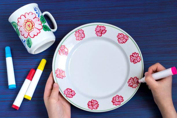 handgefertigte gemälde an geschirr marker für keramik. schritt 5 - handbemalte teller stock-fotos und bilder