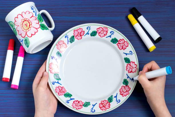 handgefertigte gemälde an geschirr marker für keramik. schritt 6 - handbemalte teller stock-fotos und bilder