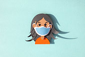 istock Handmade paper art girl in a face mask protective for spreading of virus. 1217151393