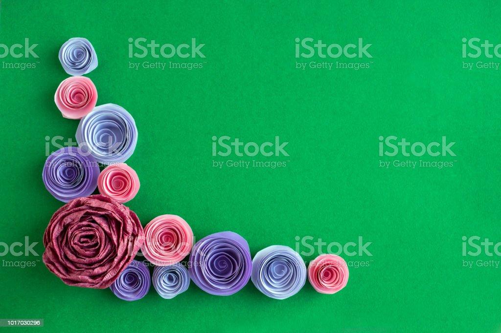 Handmade paper flowers angled frame on a green background beautiful handmade paper flowers angled frame on a green background beautiful pink lilac purple mightylinksfo