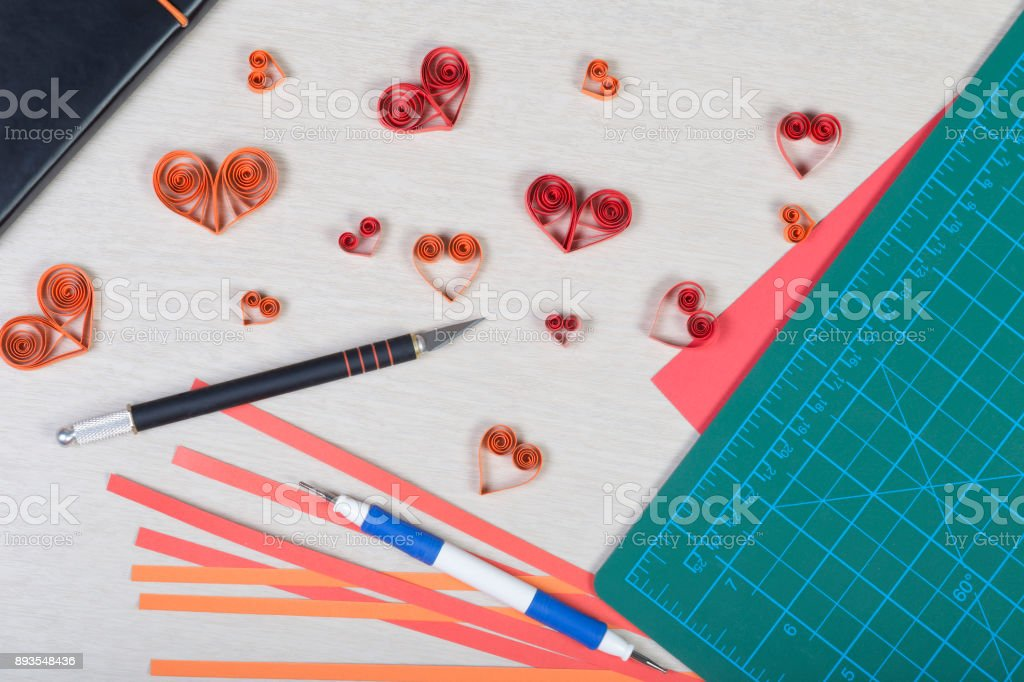 Handmade paper hearts with tools for quilling (paper strips, slotted tool, knife, cutting mat) on light wooden background. Preparation for Valentine's day, wedding or other romantic event. stock photo