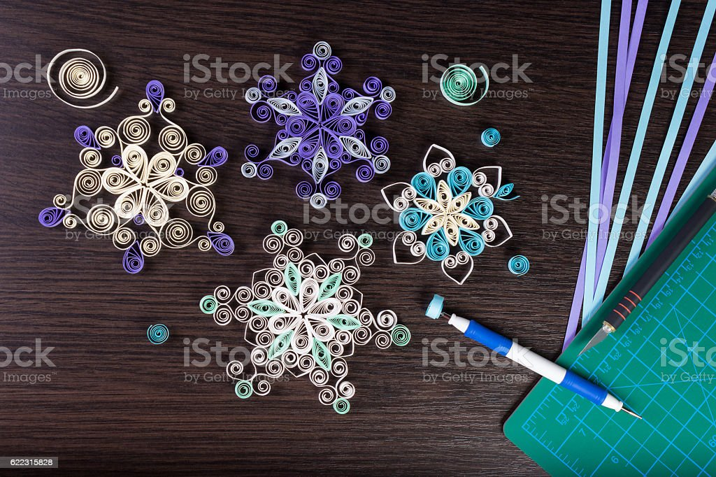 Handmade paper snowflakes with tools for quilling stock photo