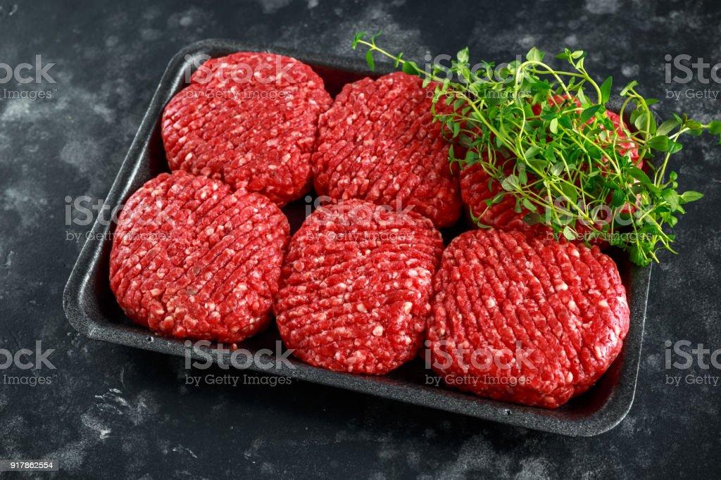 Handmade raw butchers steak burgers on marble chopping board stock photo
