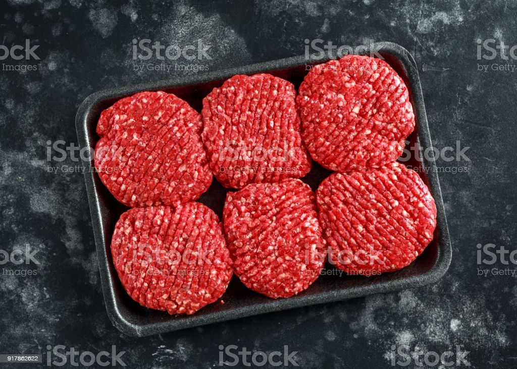 Handmade raw butchers steak burgers on marble chopping board stock photo