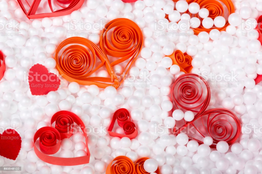 Handmade red and orange paper hearts surrounded by small white foam balls. Close shot. Top view. stock photo