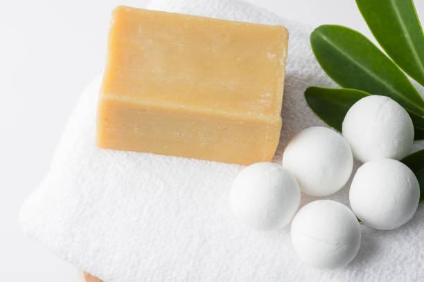 Handgefertigte Salzbadebomben in Kugeln Form aus organischen veganen natürlichen Zutaten handgefertigte französische Marseille-Seife auf weißen Handtuch-Grünpflanzen. Wellness Körperpflege Wellness – Foto