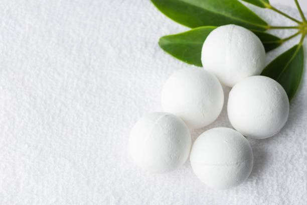 Handgemachte Salzbadebomben in Kugeln formen aus organischen veganen Naturstoffen auf weißen Handtuchgrünenhauspflanzen. Wellness Body Care Wohlfühl-Konzept – Foto