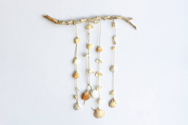 Handmade seashell mobile. Seashells hanging in the middle of a white background. Sea and summer decoration. stock photo
