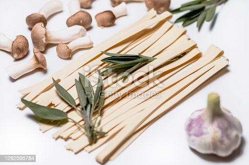 istock Handmade spaghetti with sage, herb side and garlic against a white background 1292595784