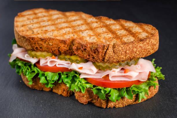 handgemachte leckere Truthahn-Sandwich mit Tomaten, Salat und Gurke, auf schwarzem Hintergrund – Foto