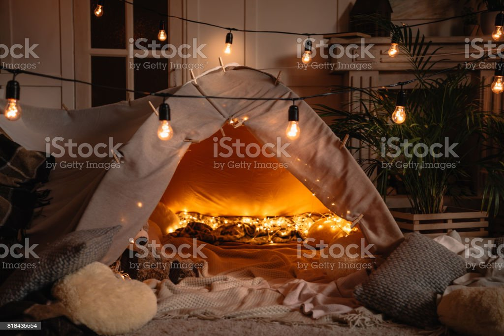 handmade tent with blankets, pillows, toys and lights in room stock photo