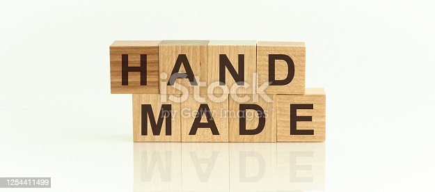 istock handmade - text on wooden cubes on a white gradient background. 1254411499