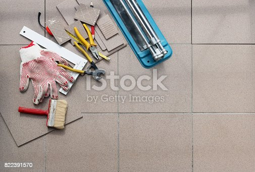 istock Handmade unprofessional adhesion of ceramic square tiles on the concrete floor of a rural house. Top view  panoramic collage 822391570