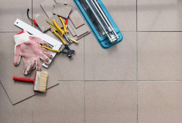 la main non professionnelle adhérence carrés de carreaux de céramique sur le plancher de béton d'une maison rurale. collage de panoramique vue de dessus - étage photos et images de collection