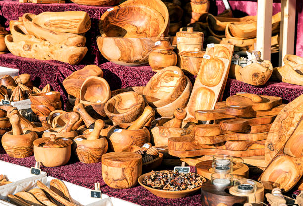 Handmade utensils, bowls, chopping board of olive wood on a outdoor stand. - foto stock