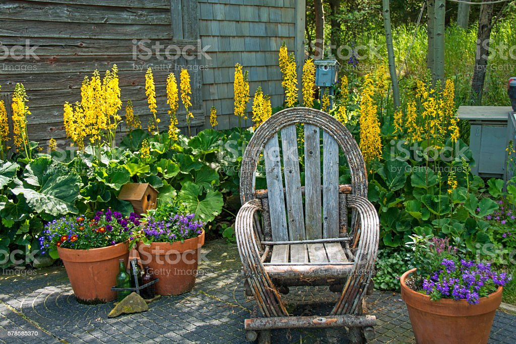 Handmade Willow Garden Chair in Summer Garden with Flowers stock photo