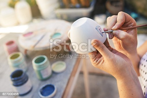 Closeup shot of a woman painting a cup in her small crafts workshop