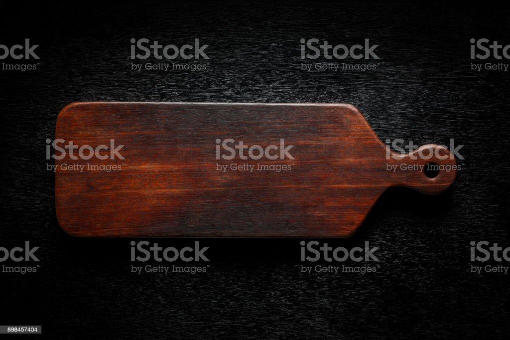 Handmade wood cutting board on black wooden board stock photo
