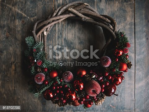 istock Hand-made wooden festive Christmas wreath with red Christmas tree decoration and spruce leaves on the old rustic wooden table background, flat lay 913702200