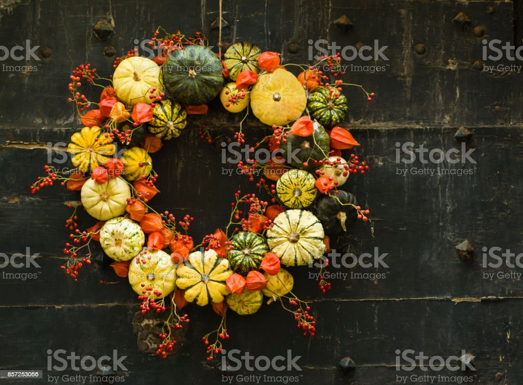 Handmade wreath of small pumpkins and zucchini on a vintage door stock photo