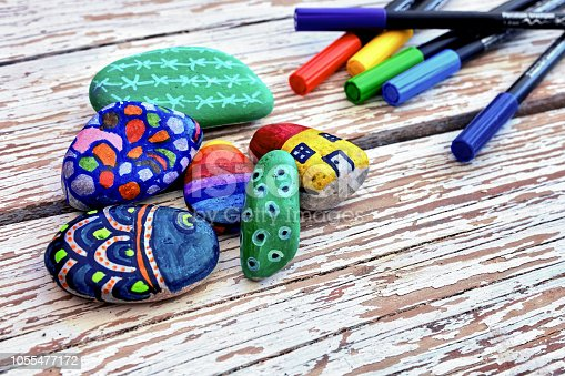 Hand-painted colorful stones and acrylic pens on a vintage textured wooden table