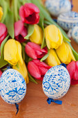 Hand-painted easter eggs with tulips on wooden background