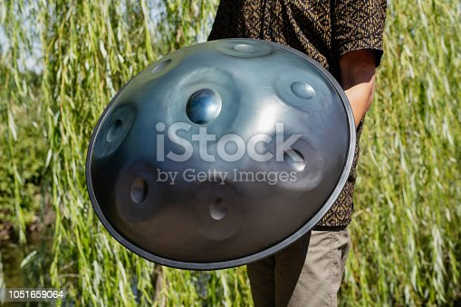 Man holding a handpan, a metal percussion instrument. Otudoors scene.
