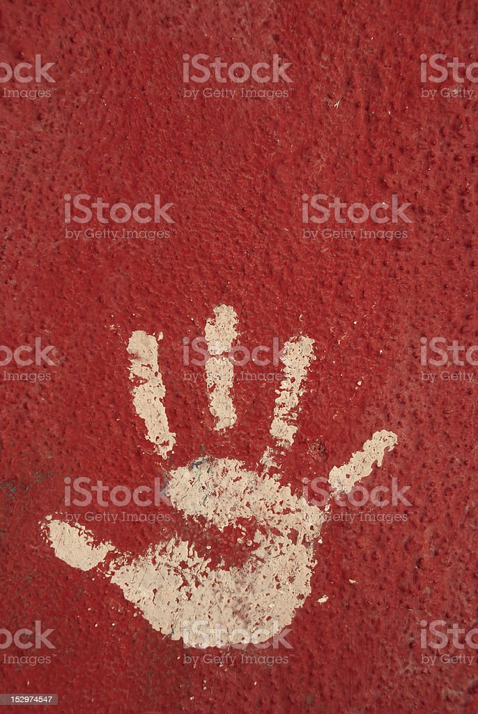 Left hand palm print on red wall
