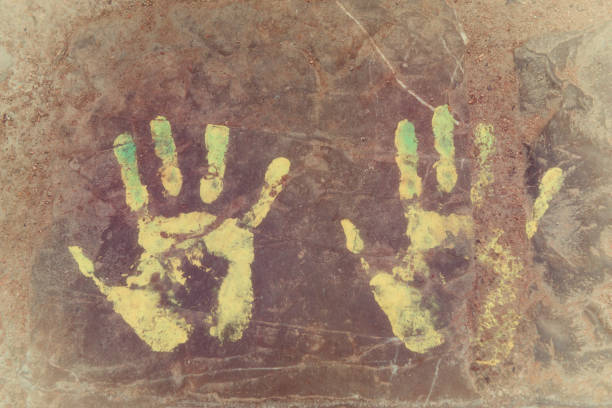 Handprints (left and right hand) on concrete floor. Vintage image with film grain. stock photo
