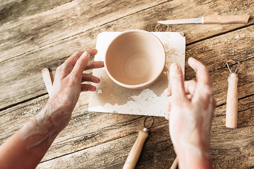 Hands above clay bowl on wooden table, artisan pov