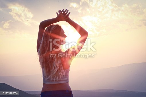 a long haired blonde female standing inferno of a sunset over the mountains with hands outstretched above head. sun is beaming through arms into a sun burst