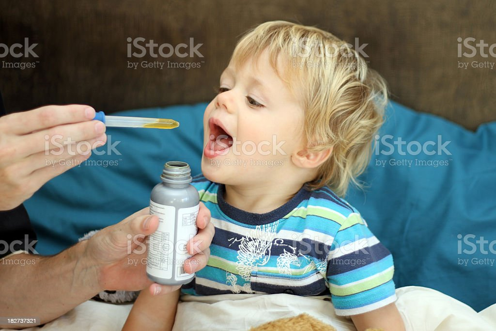 Hands administrating medicine to young boy  Little sick boy taking his medicine. Antibiotic Stock Photo
