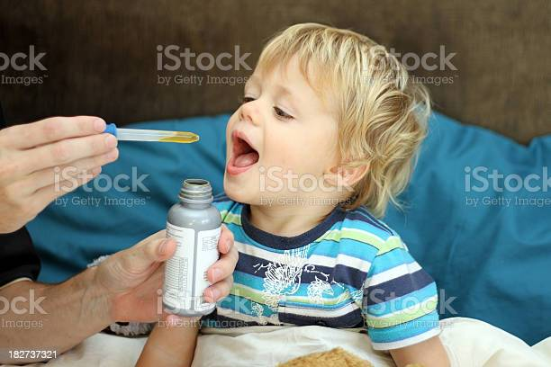 Hands Administrating Medicine To Young Boy Stock Photo - Download Image Now
