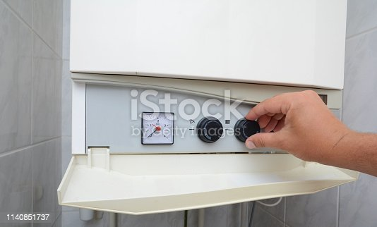 996279800istockphoto Hands adult men set the temperature of the water in the double-circuit gas boiler. 1140851737