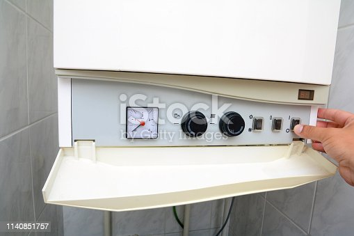 996279800istockphoto Hands adult men turning on of the water in the double-circuit gas boiler. 1140851757