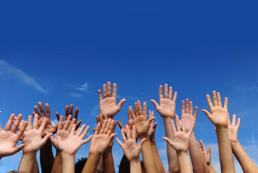 Hands against blue sky