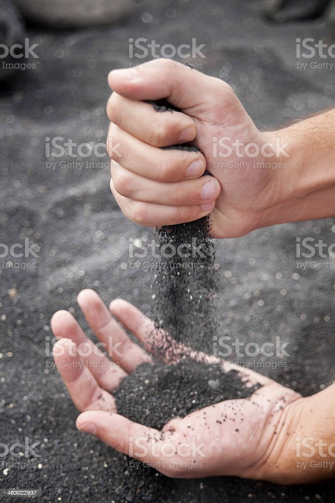Hands and black sand. stock photo