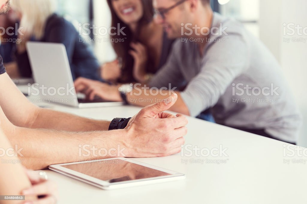 Hands and digital tablet Young people sitting at the table in an office and using laptop. Close up of male hands and digital tablet.  2015 Stock Photo