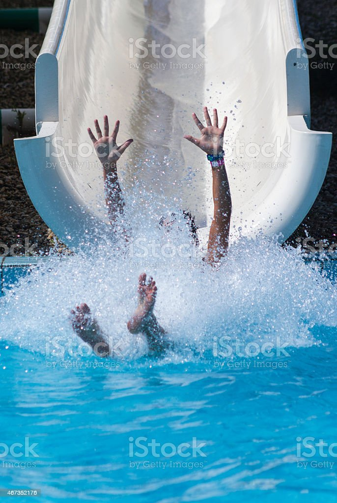 Hands and feet in a splash at the bottom of a water slide stock photo