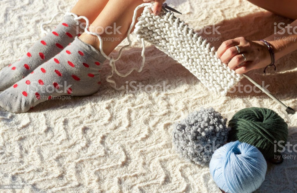 hands and feet of woman knitting cotton yarn royalty-free stock photo