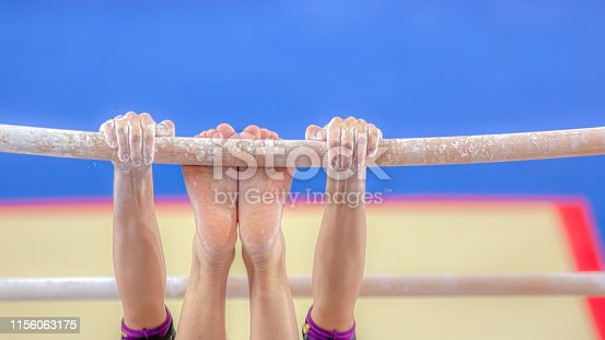 Hands and feet young girl gymnast exercises on bar