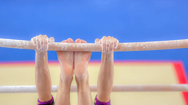 hands and feet young girl gymnast exercises on bar - uneven parallel bars stock photos and pictures
