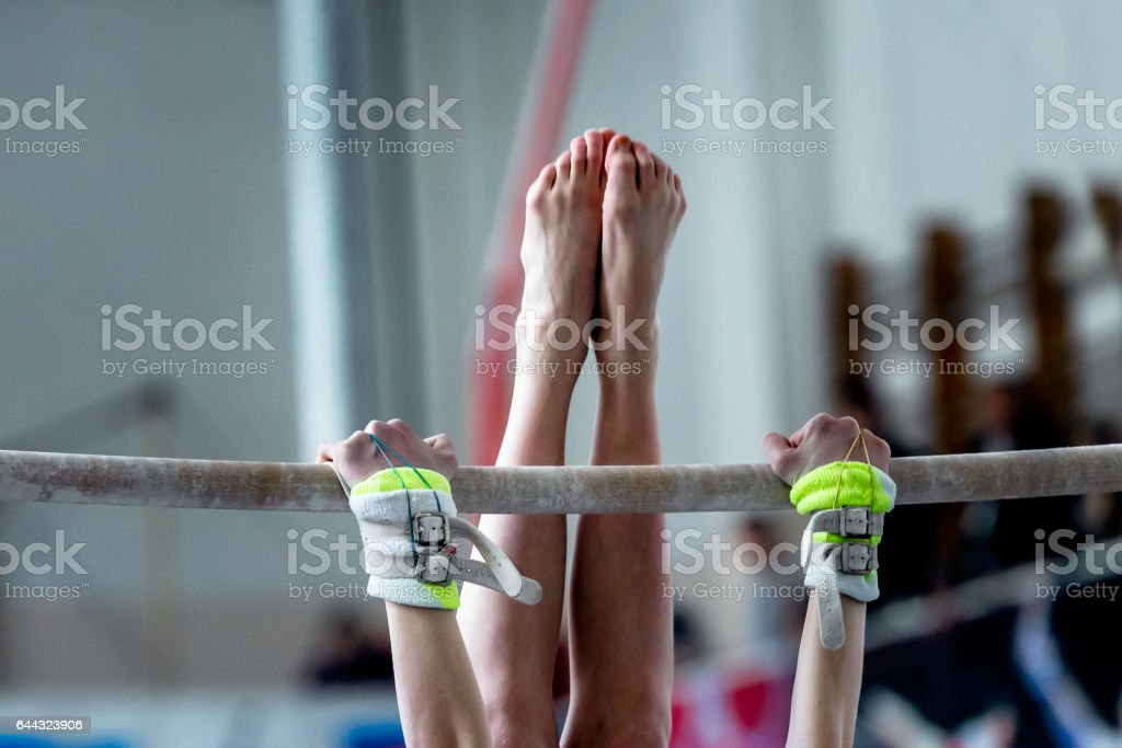 hands and feet young girl gymnast exercises on bar stock photo