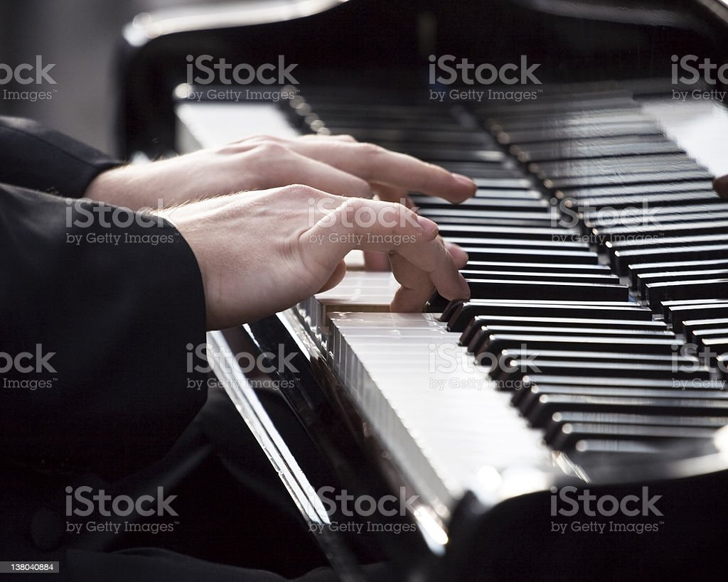 Hands and fingers of a pianist glide across piano keys stock photo