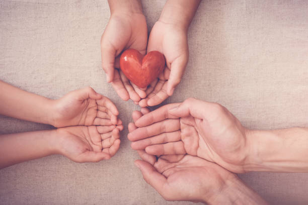hands and red heart, health insurance, donation and charity concept stock photo