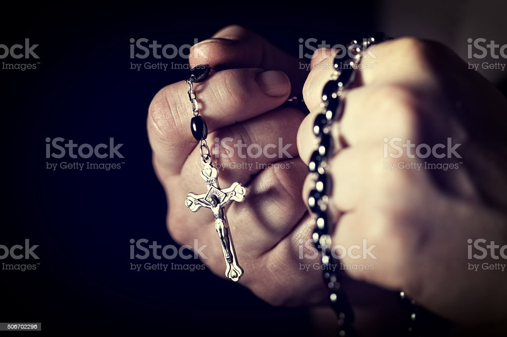 hands and rosary stock photo