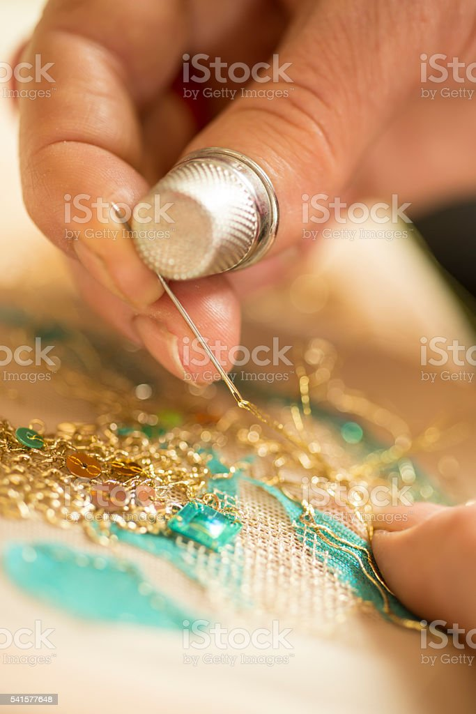 Hands and thimble doing embroidery with gold thread stock photo