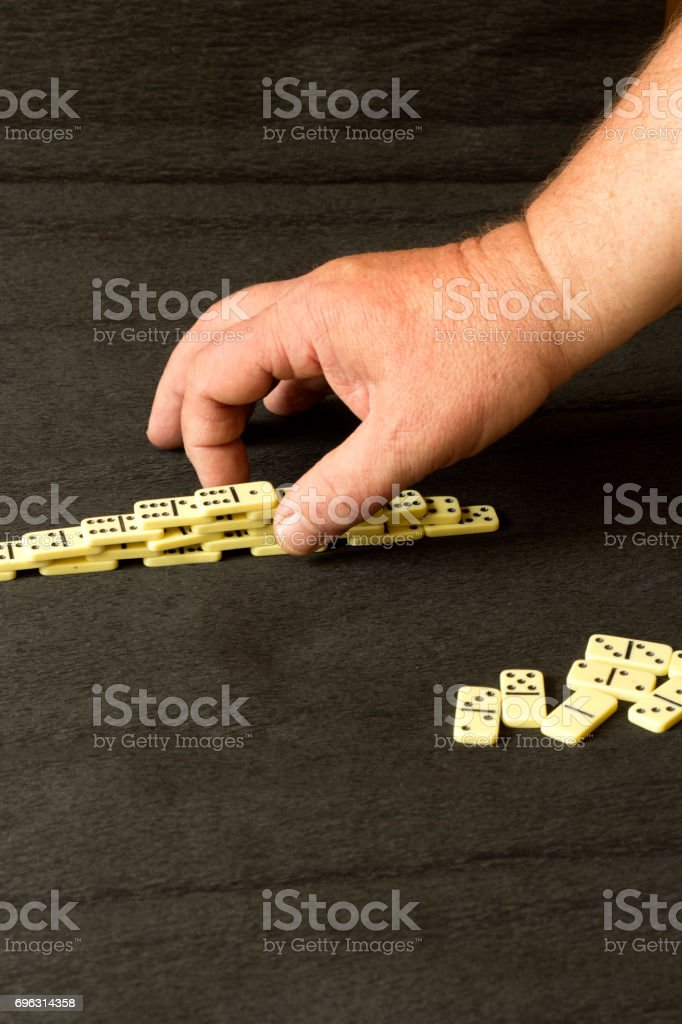 Hands and white dominoes stock photo