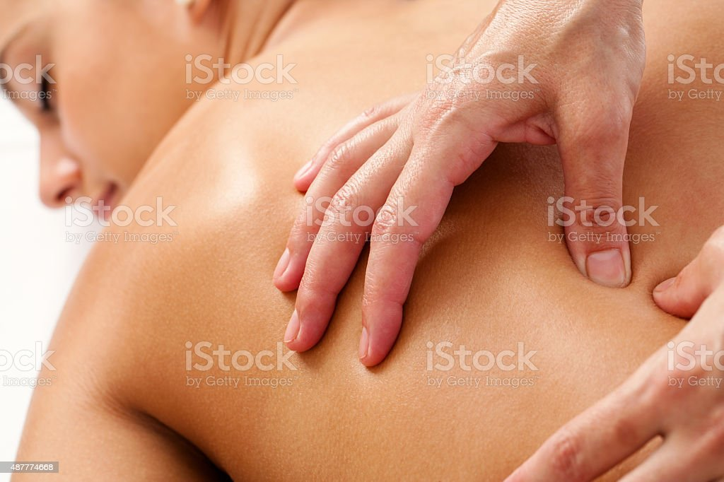 Hands applying pressure on female back in spa. stock photo