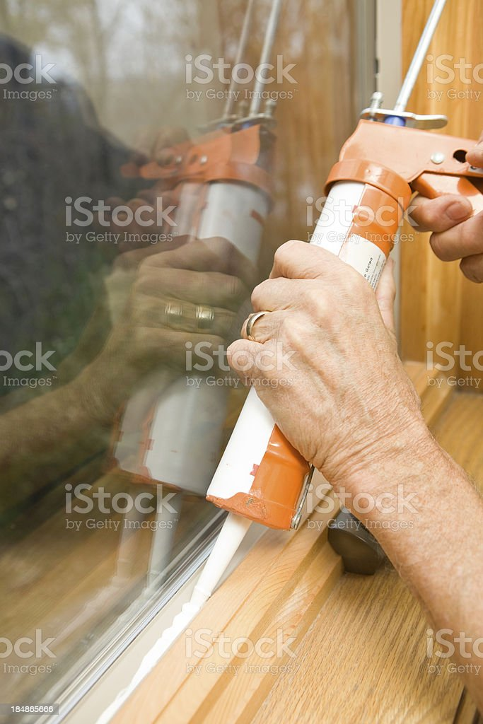 Hands Applying Weather Seal Caulk to Window Frame stock photo